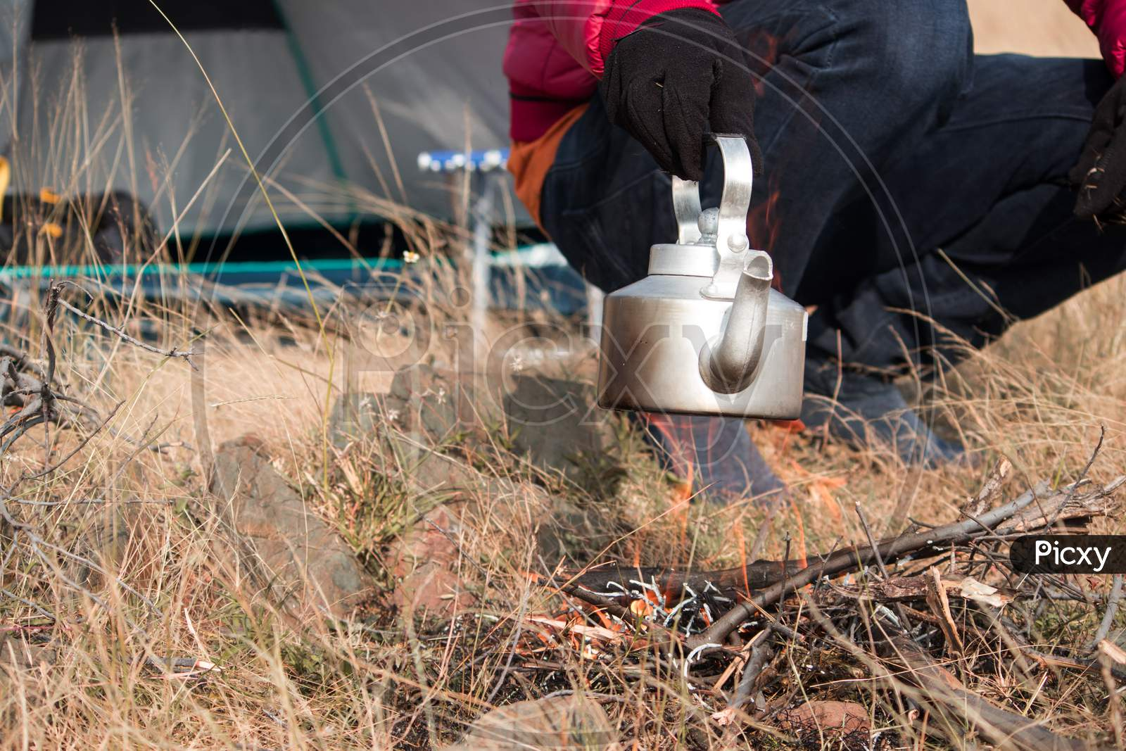 Close Up Shot Of Hiker Heating Up Teapot Or Coffee Using Campfire During Camping.