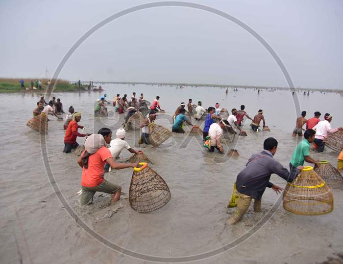 villagers participating in community fishing as part of Bhogali Bihu celebrations are seen through a traditional fishing tool at Dighali Lake in Nagaon district, in the northeastern state of Assam on Jan 13,2021