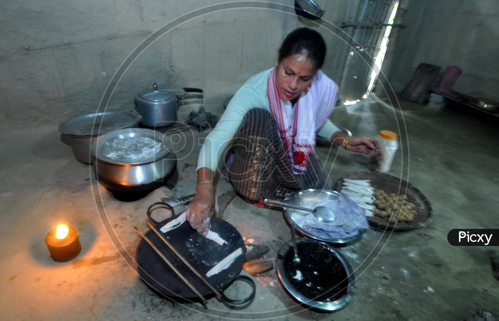 A Woman making  pitha on the eve of Bhogali Bihu Festival In Mayong Village In Morigaon District Of Assam, Jan. 11, 2021.