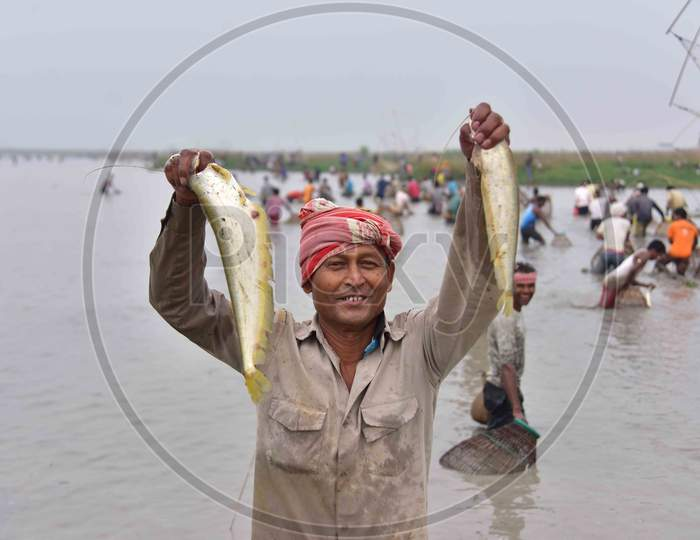 An Indian villager shows his catch as he participates in community fishing as part of Bhogali Bihu celebrations at Dighali Lake in Nagaon district, in the northeastern state of Assam on Jan 13,2021