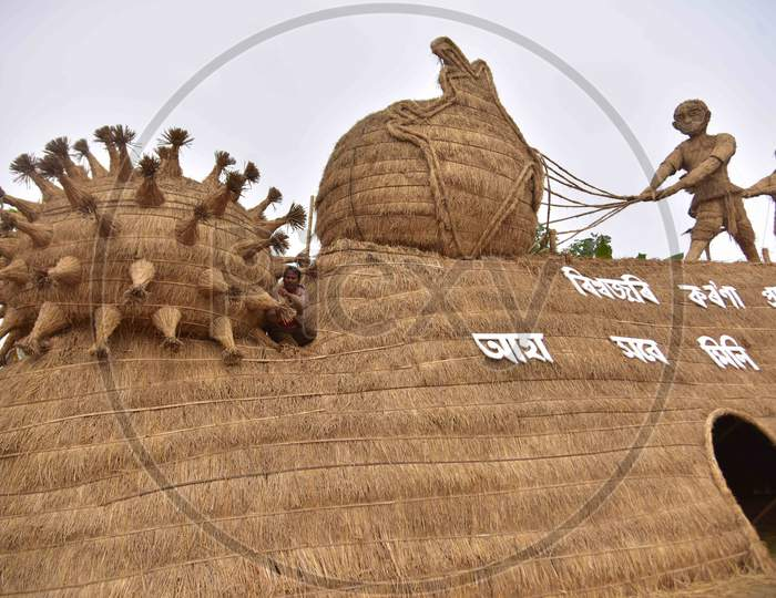 Workers prepare a makeshift cottage called Bhelaghar with protecting the world from COVID-19 as a theme ahead of the Magh Bihu festival in Nagaon district, in the northeastern state of Assam on Jan 13,2021