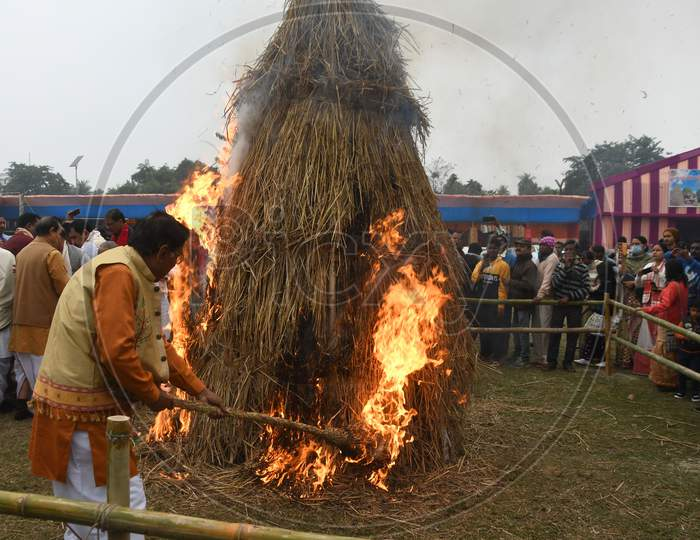 """People burning a """"Meji"""" which is made of bamboo and straw during """"Bhogali Bihu"""" celebrations in Nagaon district of Assam on Jan 14,2021."""
