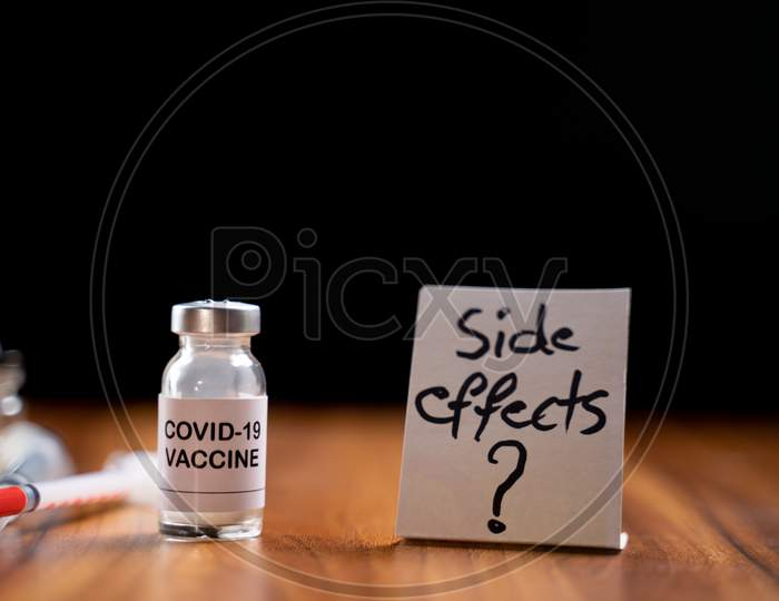 Concept Of Coronavirus Covid-19 Vaccination Side Effects Doubts And Questions Showing With Vaccine Bottle.