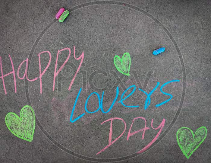 The Inscription Text On The Grey Board, Happy Lovers Day With Love Symbols. Using Color Chalk Pieces.