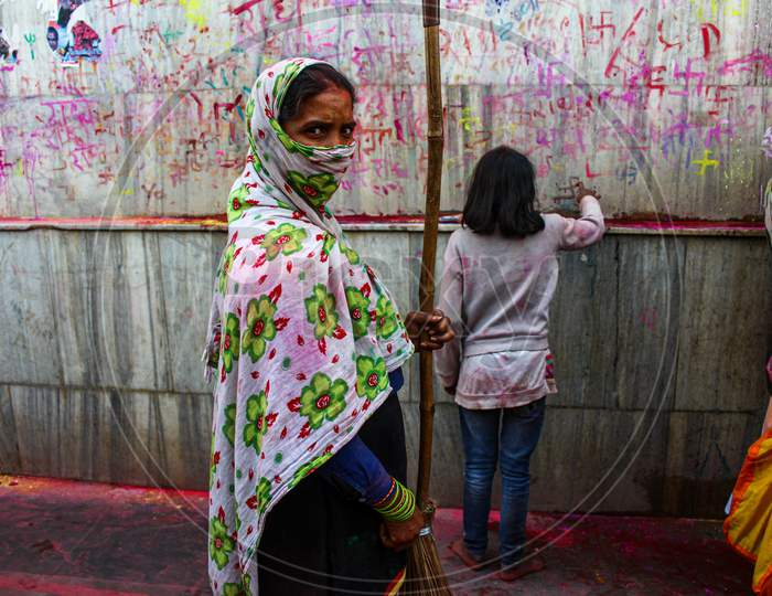 Mathura, Uttar Pradesh, India- January 6 2020: A Female Worker With Her Face Covered With A Cloth Cleaning The Temple Of Nandgaon During The Celebration Of Holi.