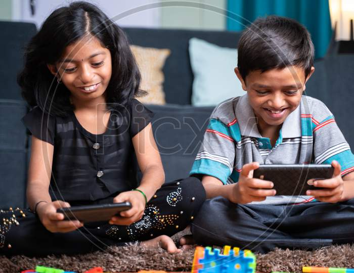 Two Young Sibling Kids Playing Online Video Game On Mobile Phone At Home - Concept Of Smartphone Game Addiction. Holidays, Modern Technology Lifestyle.