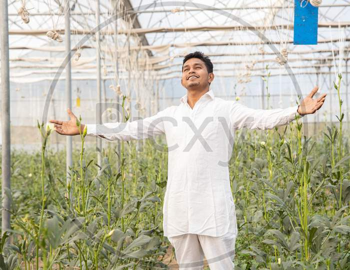 Young Happy Indian Farmer Standing With Open Arms At His Poly House Or Greenhouse, Agriculture Business And Rural Prosperity Concept. Man Wearing White Kurta Pajama Cloths, Copy Space.