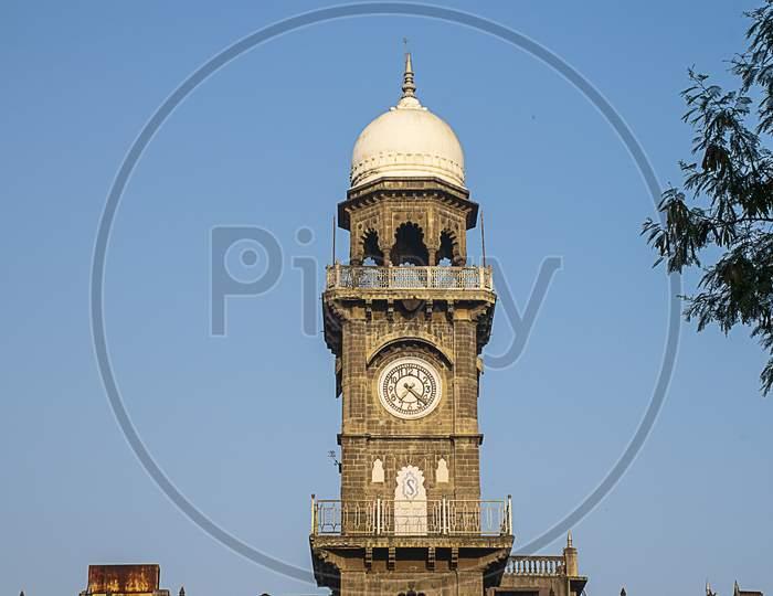 Front View Of Royal Old Exterior Clock Tower At Shalini Palace Hotel, Kolhapur City India.