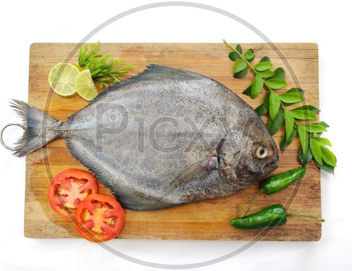 Fresh Black Pomfret Fish Decorated With Herbs And Vegetables On A Wooden Pad,Selective Focus.