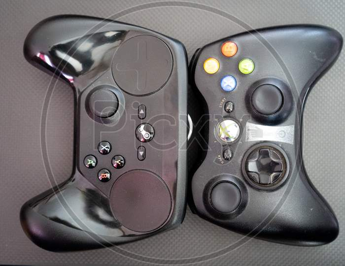 Xbox Vs The Steam Controller On A Carbon Fiber Background Showing Technology Of Inputs For Computer Gaming