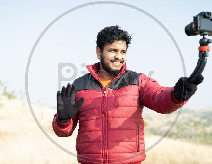 Young Traveller Busy Talking With Camera On Top Of Mountain - Concept Of Travel Vlogger, Blogger Or Influencer Recording Video During Hiking.