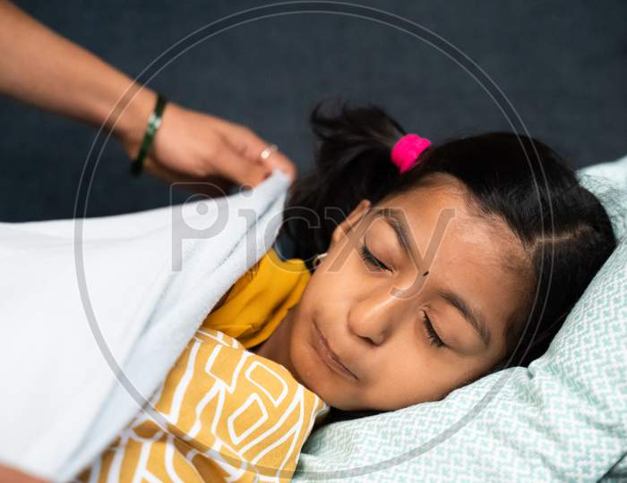Mother Covering Child With Blanket While Kid Sleeping On Sofa - Concept Of Motherhood, Love Of Mother, Relationship And Bonding.