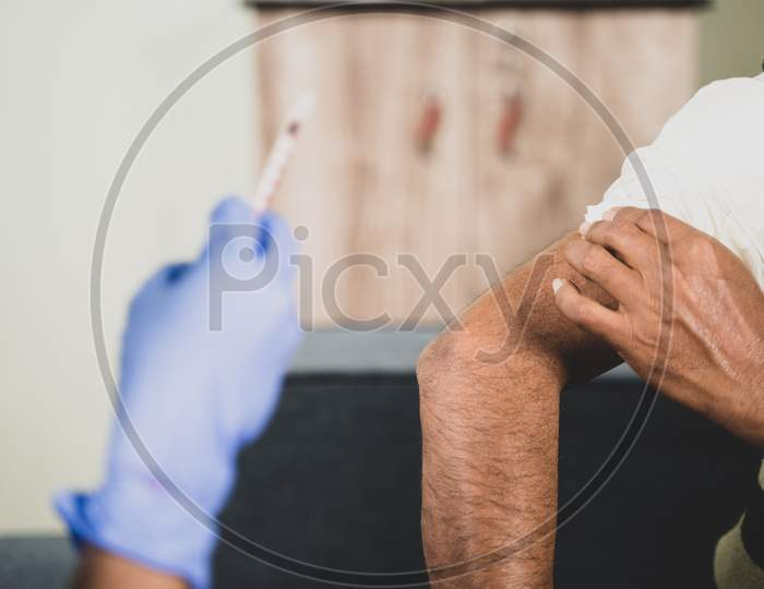 Close Up Hands Of Doctor Hands Given Vaccination Shot To Elderly Patient By Syringe Or Injunction, Patient Rubbing His Shoulder At Home - Concept Of Coronavirus Covid-19 Vaccination.