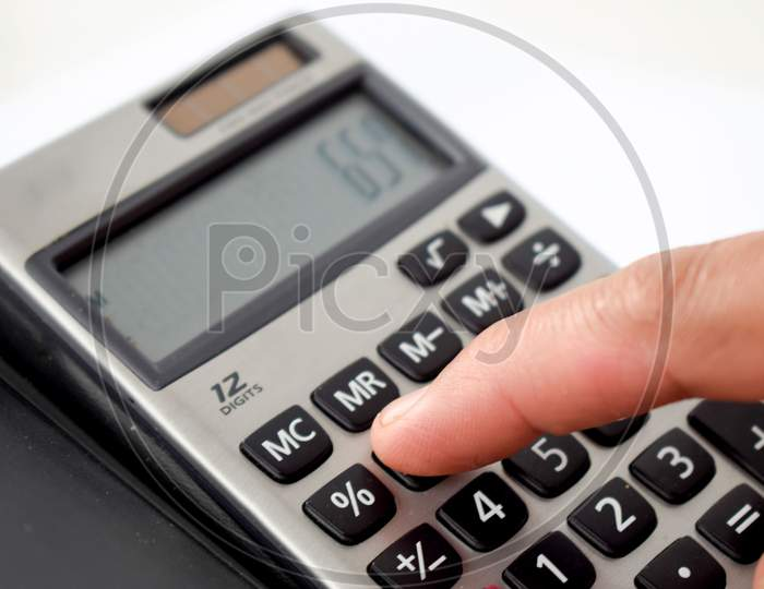 Close up photo of finger and calculator to calculate economy and finance