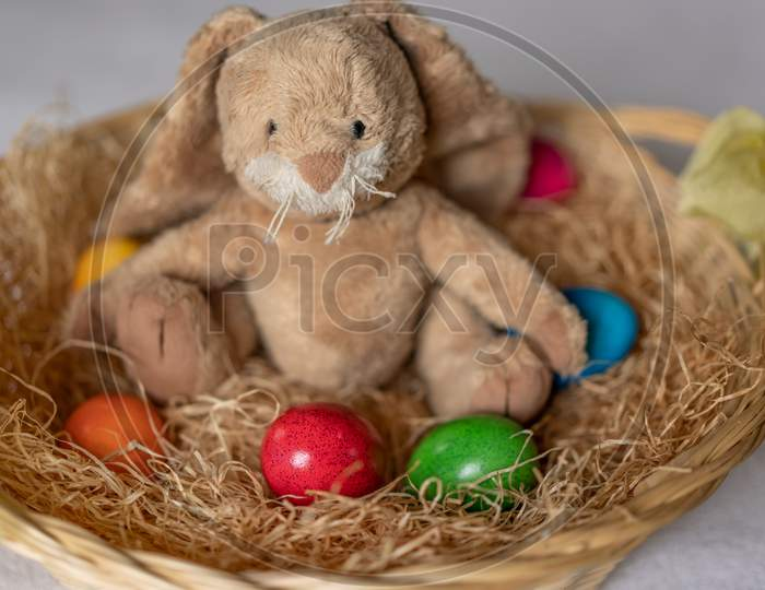 Stuffed Easter Bunny In Hay Basket And Eggs.