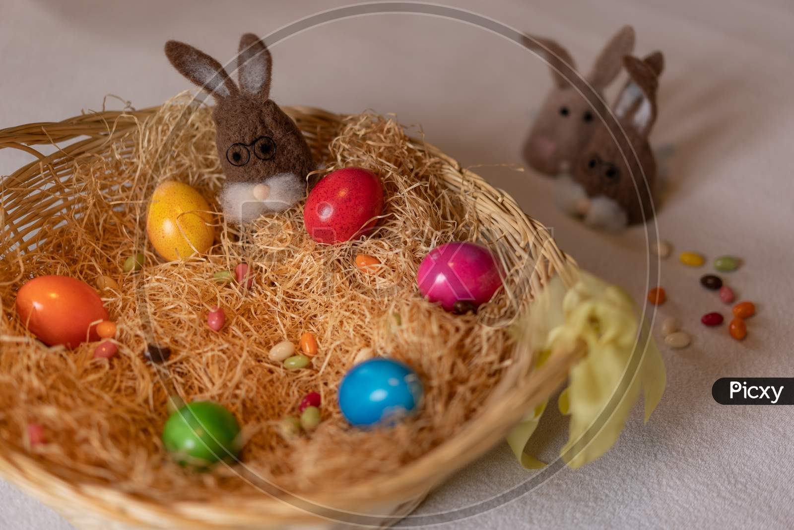 Colored Easter Eggs And One Brown Felt Bunnies In And Two Separated Other Out Of The Nest Of Straw With Colorful Sweet Sugar Eggs.