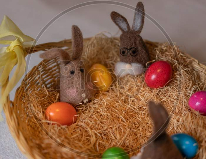 Brown Felt Bunnies With Multicolored Easter Eggs In Nest Of Straw With Colorful Sweet Sugar Eggs.