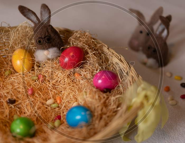 Colored Easter Eggs And Caps Of Brown Felt Bunnies In Nest Of Straw With Colorful Sweet Sugar Eggs. Felt Bunnies To Keep Eggs Warm.