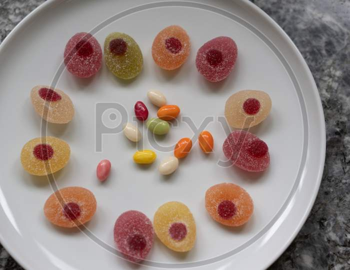 Sweeties For Easter. Easter Candies In A Circle On A White Plate On A Gray Granite Table.