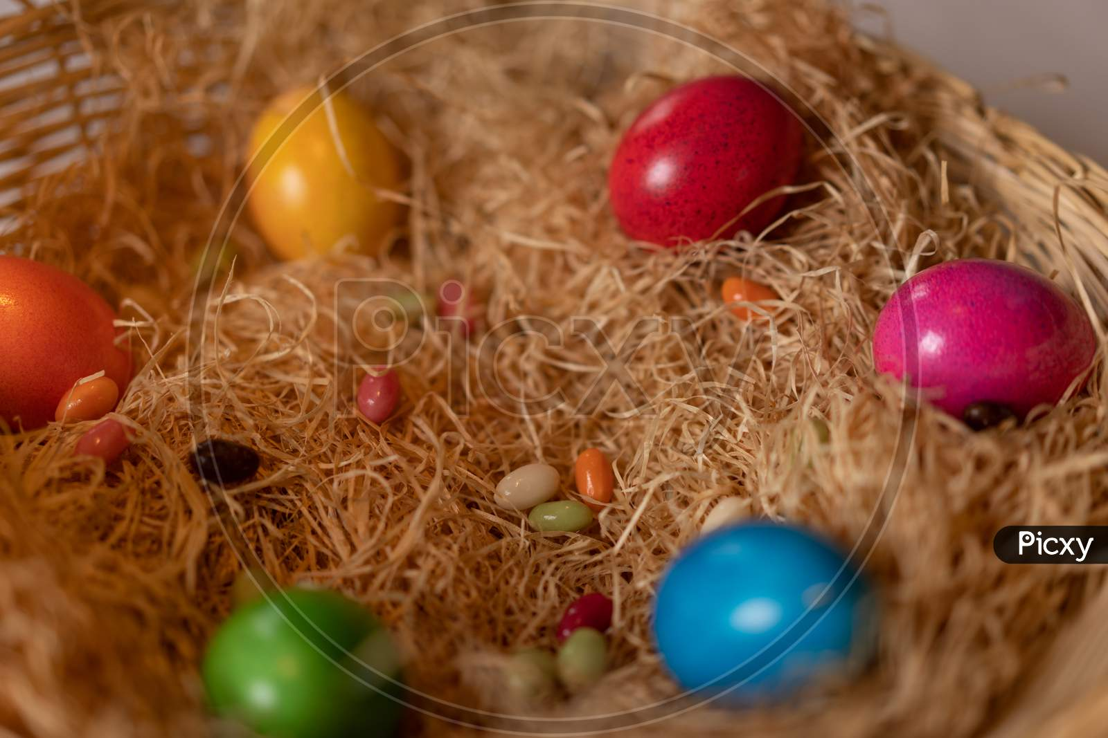Colorful Cooked Easter Eggs And Candy Eggs In Hay Basket.