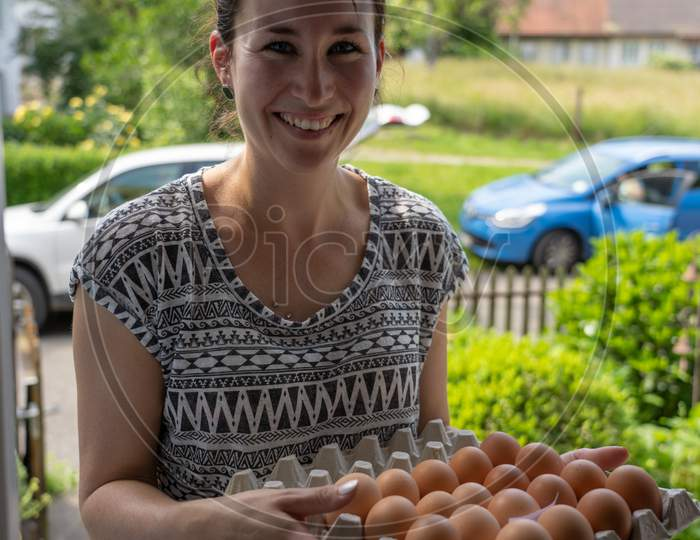 Delivery Of Fresh Eggs At The House Door By A Young Smiling Woman.