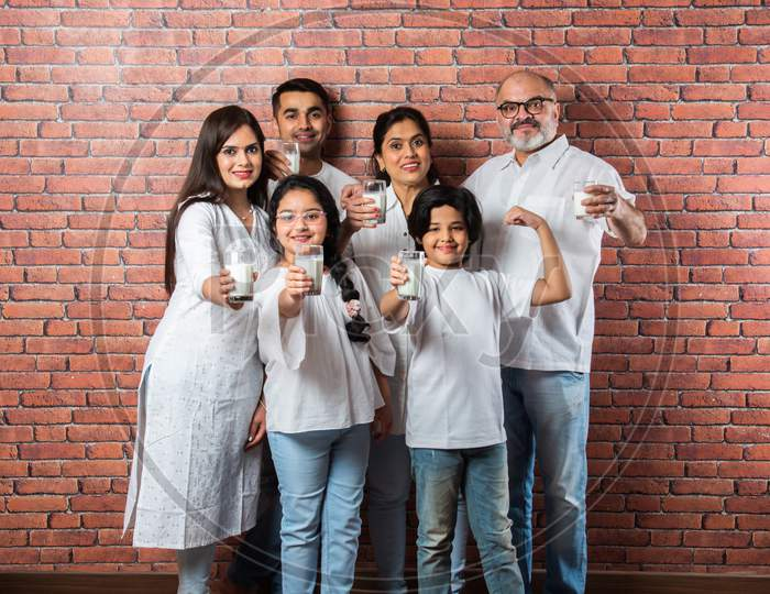 Indian Asian Family Of Six Drinking Milk In A Glass