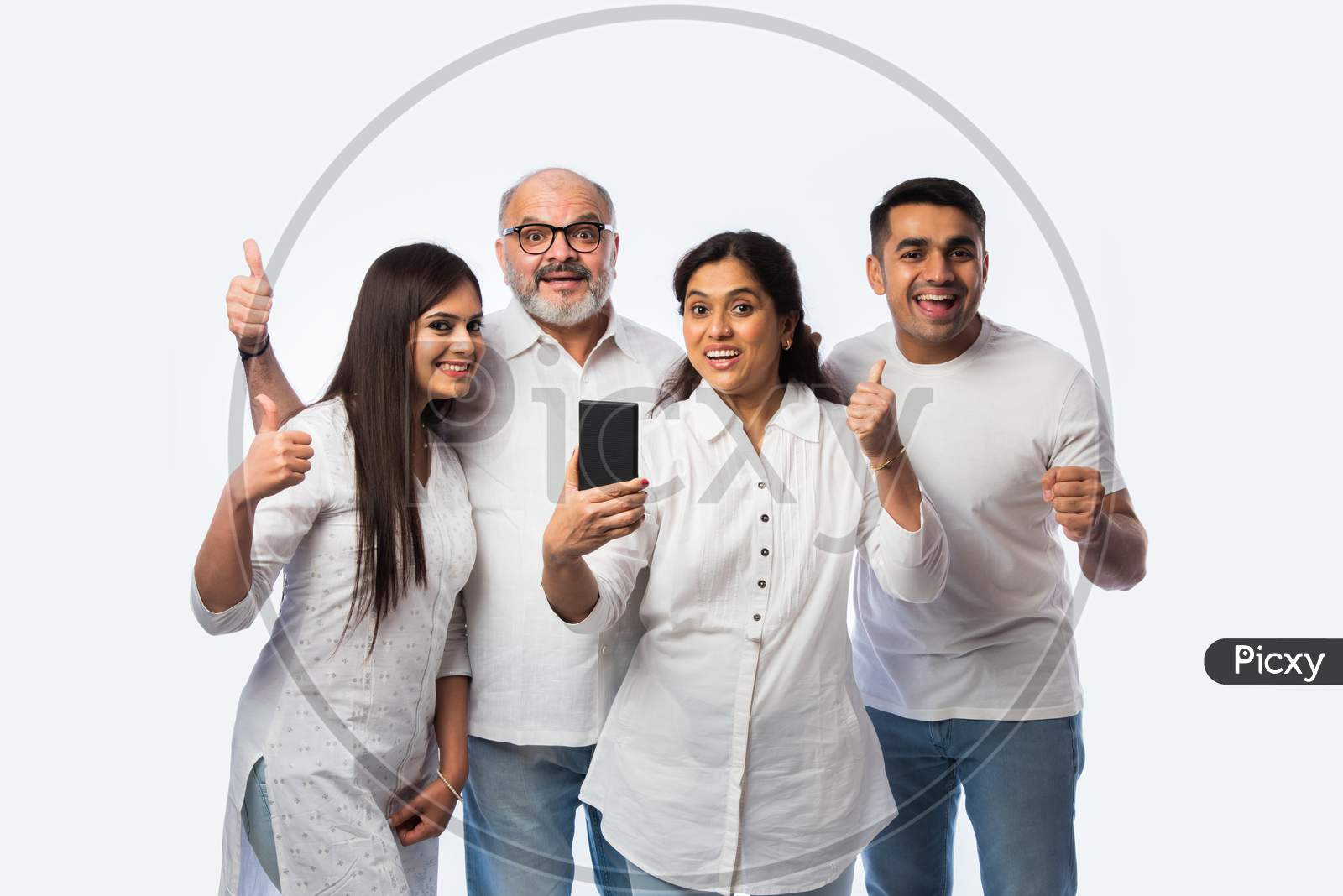 Indian Family Using Smartphone, Includes Young Couple And Senior Adults