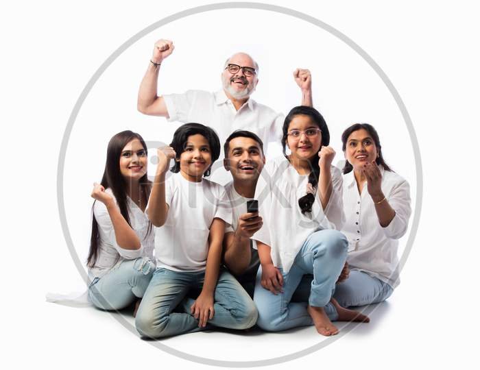 Indian Asian Family Watching Tv, Holding Remote Control, Sitting Against White Background