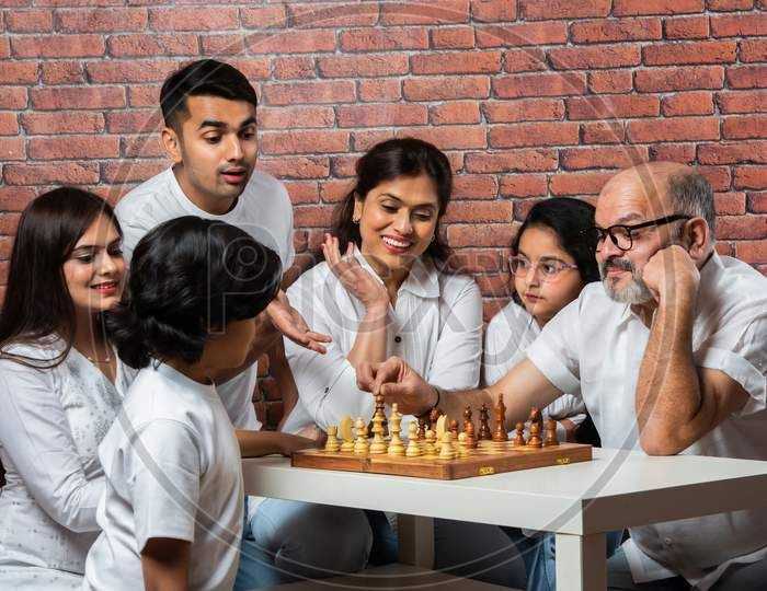 Indian Asian Multigenerational Family Playing Chess Indoor At Home In White Cloths
