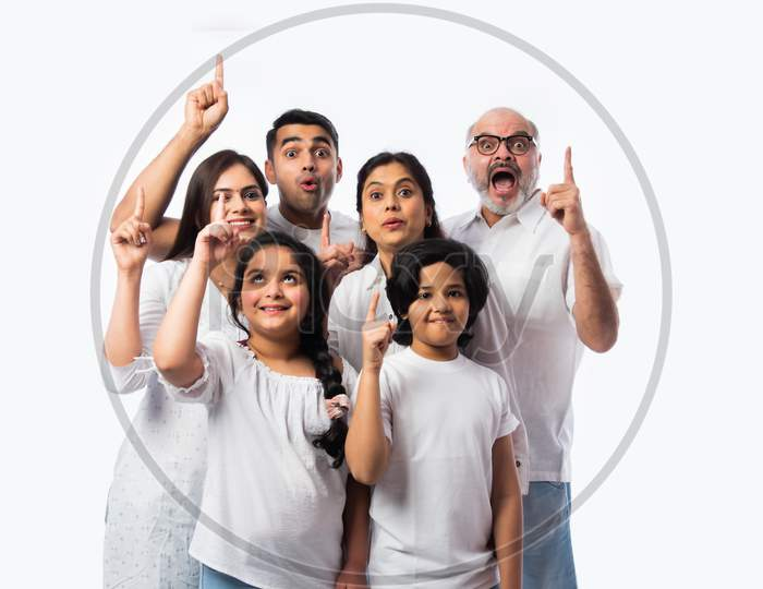 Asian Indian Family Of Six Presenting Or Pointing Empty Space While Standing Against White Backdrop