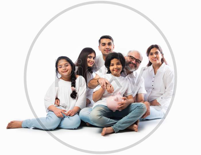 Indian Family With Piggy Bank Standing Or Sitting Isolated Against White
