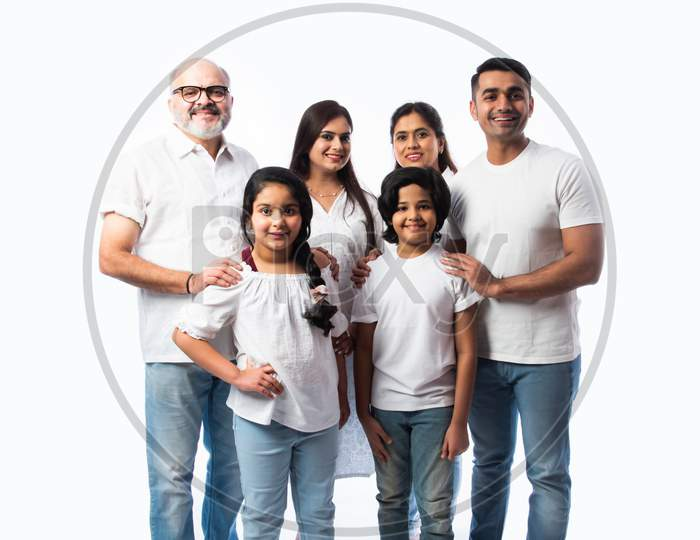 Portrait Of Indian Family With Grandparents, Parents & Kids Against White Background In White Cloths