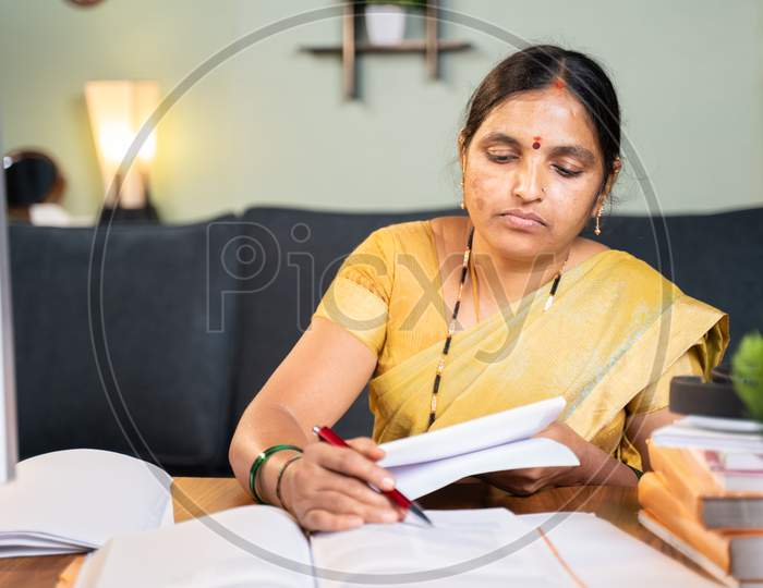 Indian Woman Professor Correcting Answer Sheets Of Books By Referring Books At Home At Working Desk.