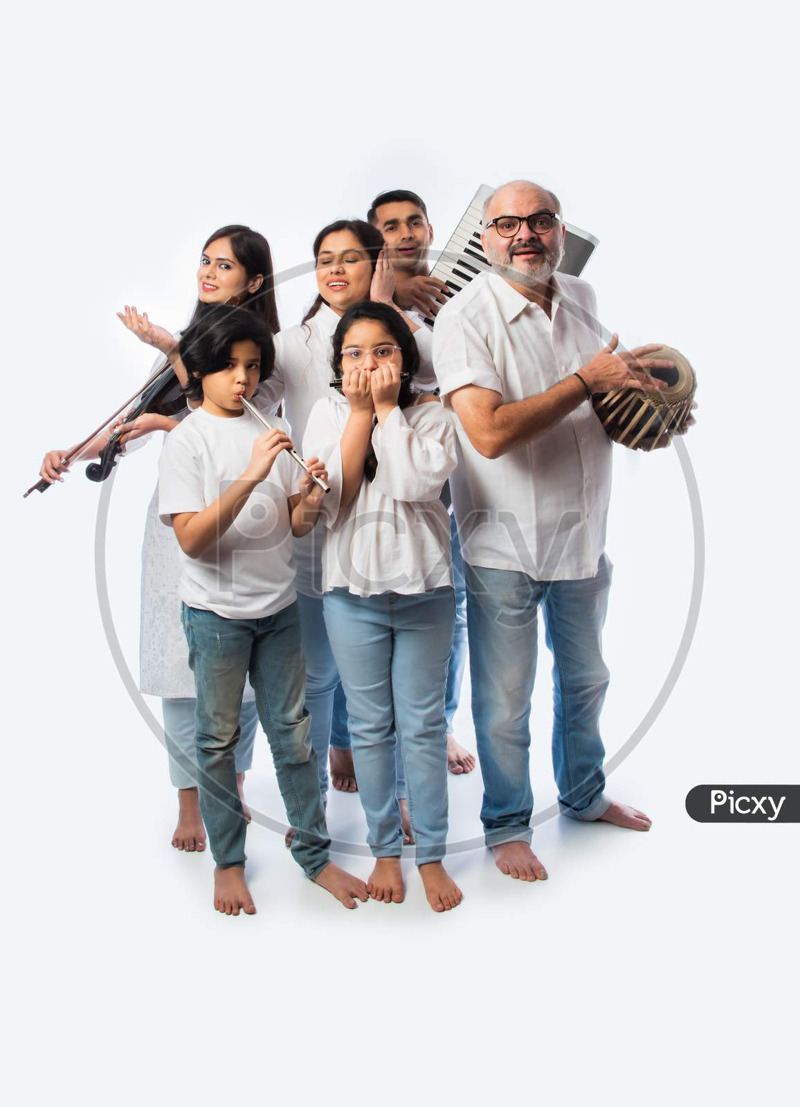 Indian Family Playing Music Instruments Together As A Band, Performing Against White