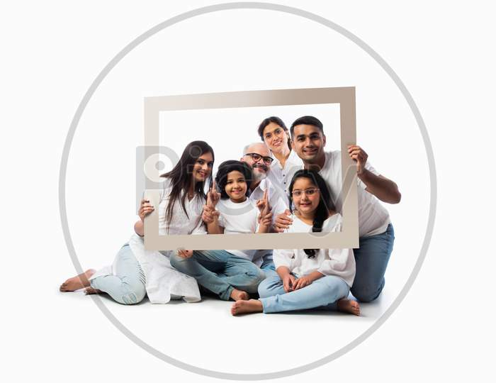 Indian Family Of Six Looking Through Or Holding Empty Frame Against White Background