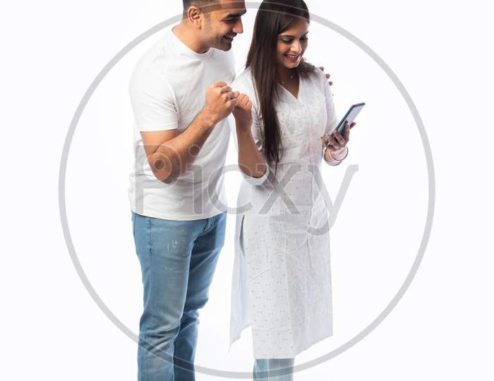 Indian Asian Smart Young Couple Holding Using Smartphone Against White Background