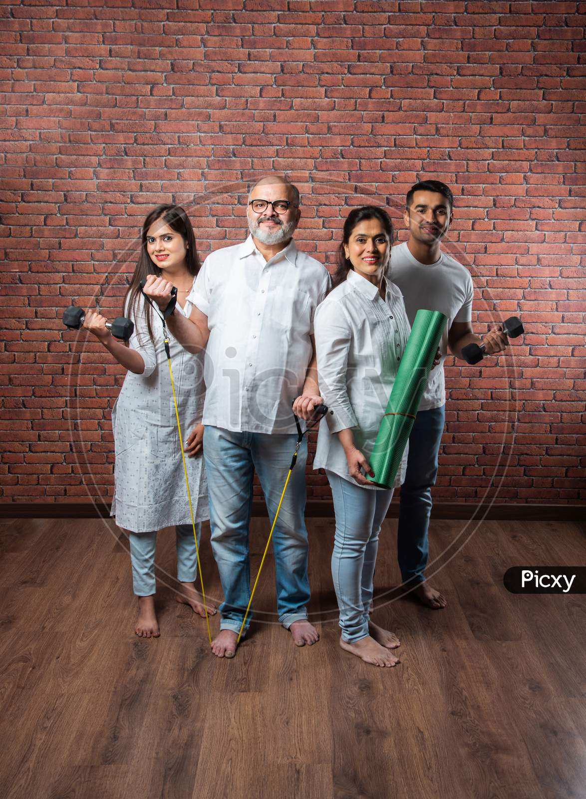 Indian Asian Family Exercising Together At Home - Healthy Lifestyle Concept