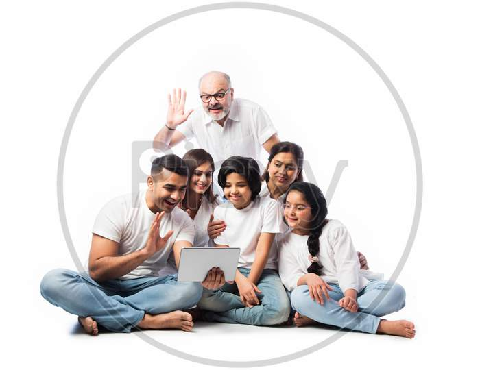 Happy Indian Family Shopping Online Using Laptop And Credit Or Debit Card While Sitting Isolated