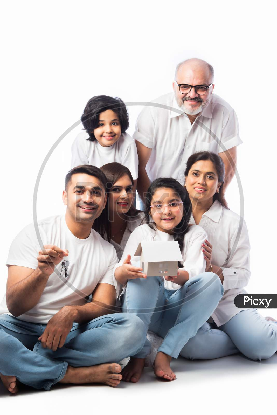 Asian Indian Family Of Six Holding Paper House Model With Keys, Isolated Against White Background