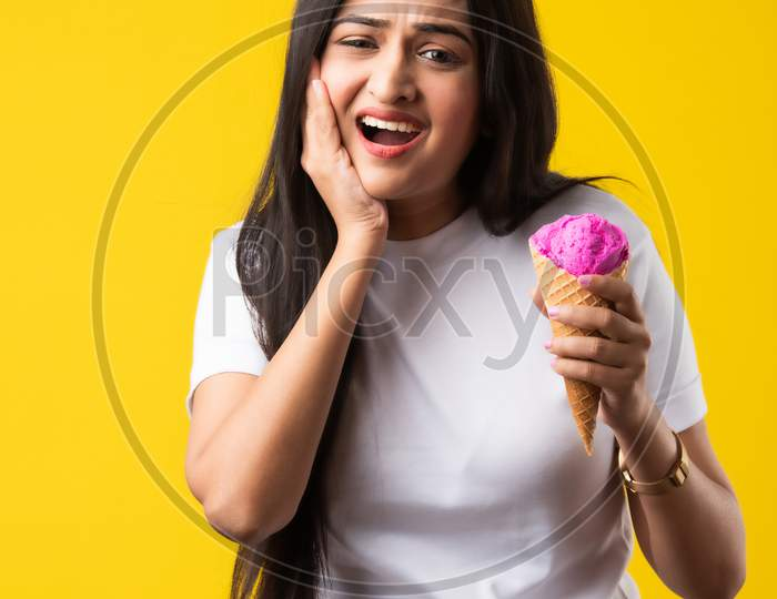 Pretty Young Indian Woman With Sensitive Teeth And Eating Cold Ice Cream On Yellow Background