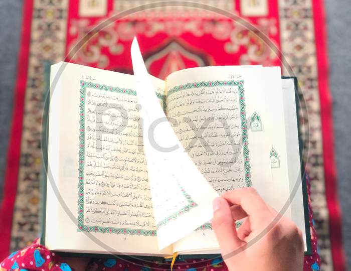 A,Woman,Reading,The,Quran,On,A,Prayer,Rug