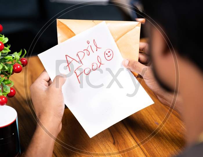 Shoulder Shot Of Young Man Receiving Prank Latter - Concept Of April Fools Day Prank Showing By Sending Surprise Letter, After Opening Mentioned April Fool In The Latter.