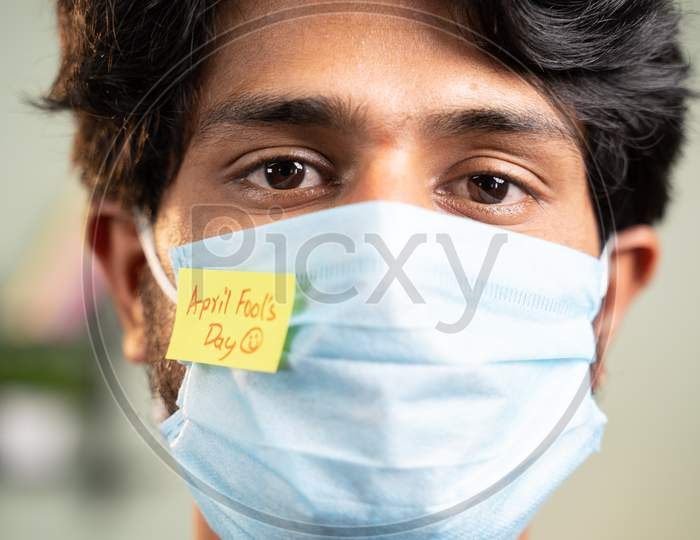 Young Man With Medical Face Mask And April Fools Day Sticker On Mask - Concept Of April Fools Day Celebrations During Coronavirus Covid-19 Pandemic.