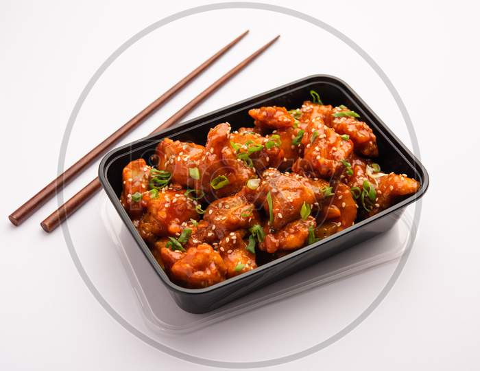 Online Food Delivery Concept In India - Tasty Chilli Chicken Packed In A Black Plastic Box