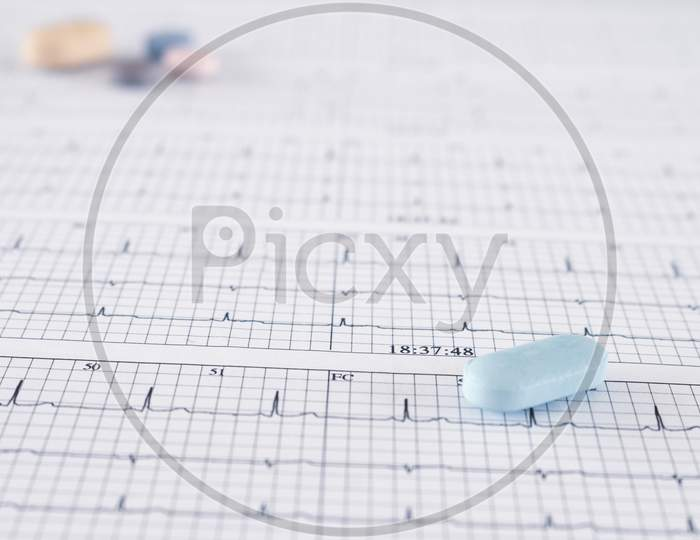 Huge Orange-Yellow Pills On Paper With Ekgs And Cardiac Arrhythmias. Medications For The Heart.