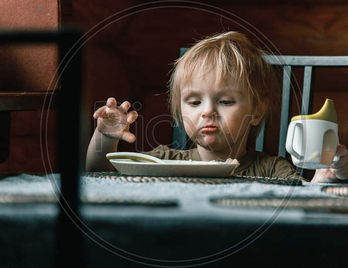 A Toddler Boy On A Chair Holds A Plastic Spoon And Eats His Lunch. Feeding Process. An Infant Child Learns To Eat. Baby Food, Family, Child, Food