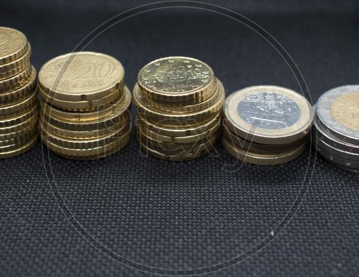 Euro Coins Stacks On Black Background In Different Positions.Euro Coins Stacked In Different Combinations