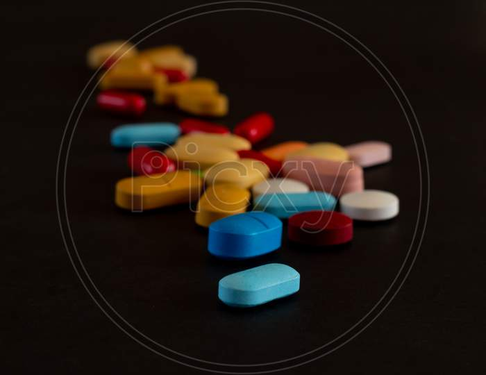 Pills Of Colors On A Neutral Black Background. Selective Focus Of Legal Drugs