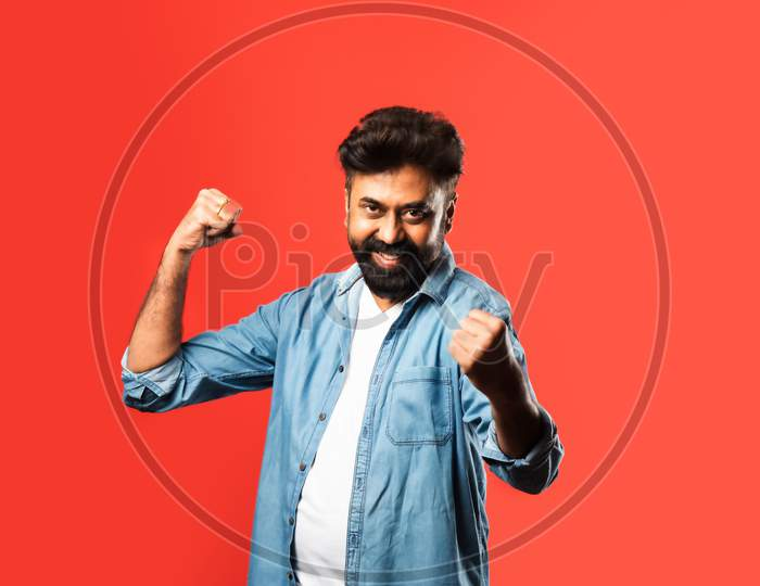 Portrait Of A Satisfied Young Indian Man Celebrating Success Isolated Over Red Background