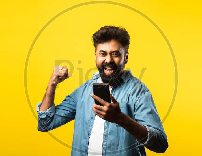 Happy Indian Bearded Young Man Using Smartphone While Standing Against Yellow Background